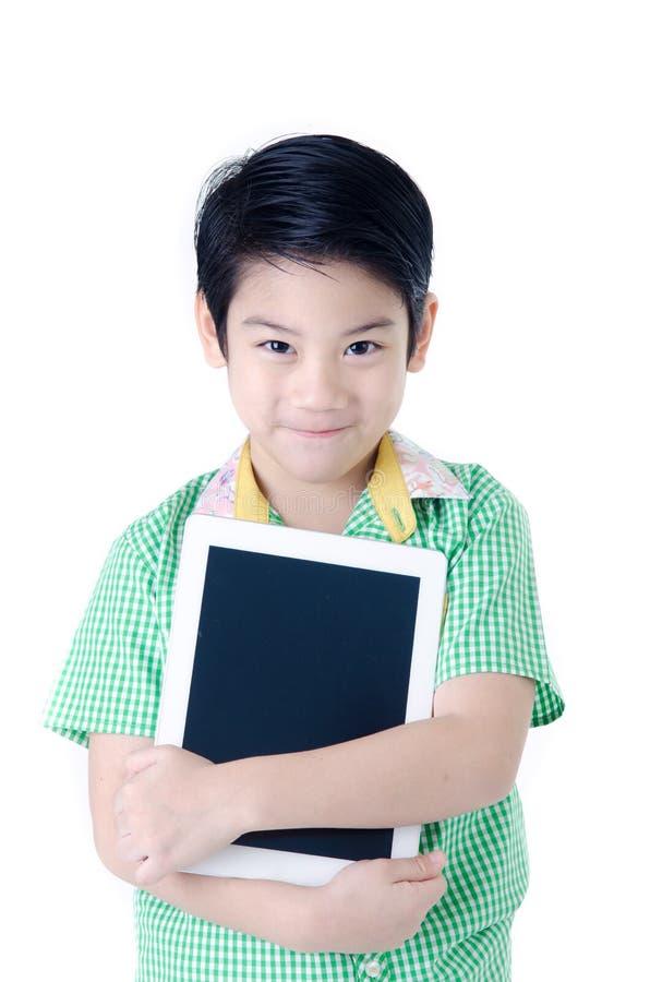 Маленький азиатский мальчик усмехается с планшетом на изолированном backgro стоковое изображение rf