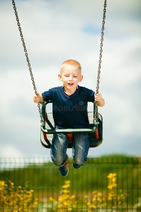 Маленький белокурый ребенок мальчика имея потеху на качании внешнем стоковая фотография rf