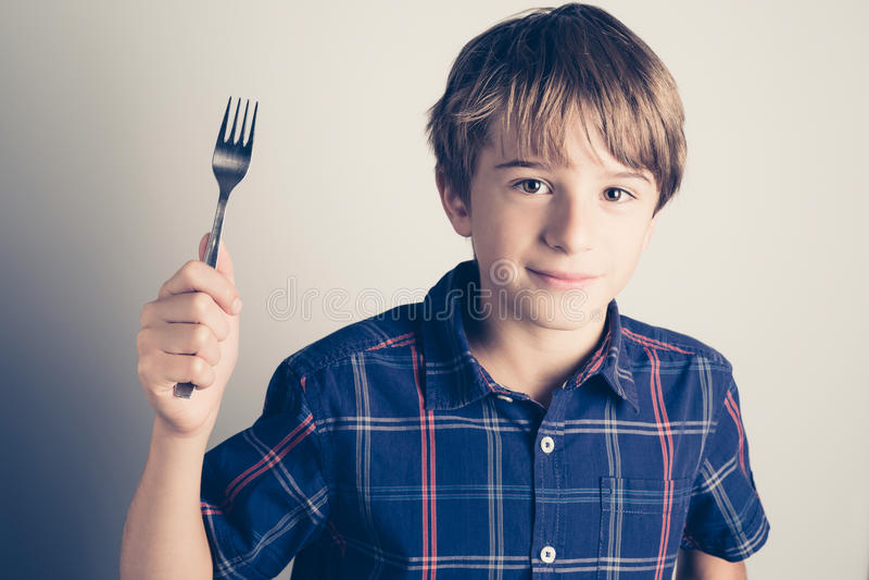 Маленький голодный мальчик с вилкой готовой для еды стоковые изображения rf