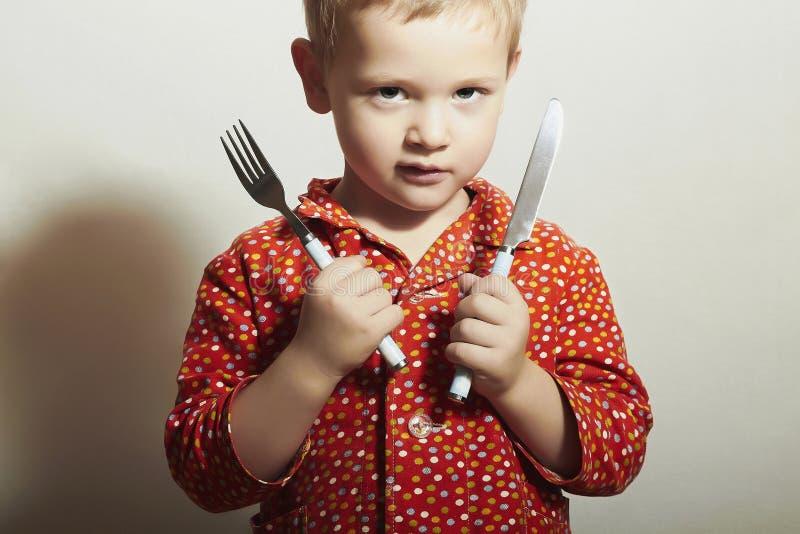 Маленький красивый мальчик с вилкой и Knife.Hungry стоковое изображение rf