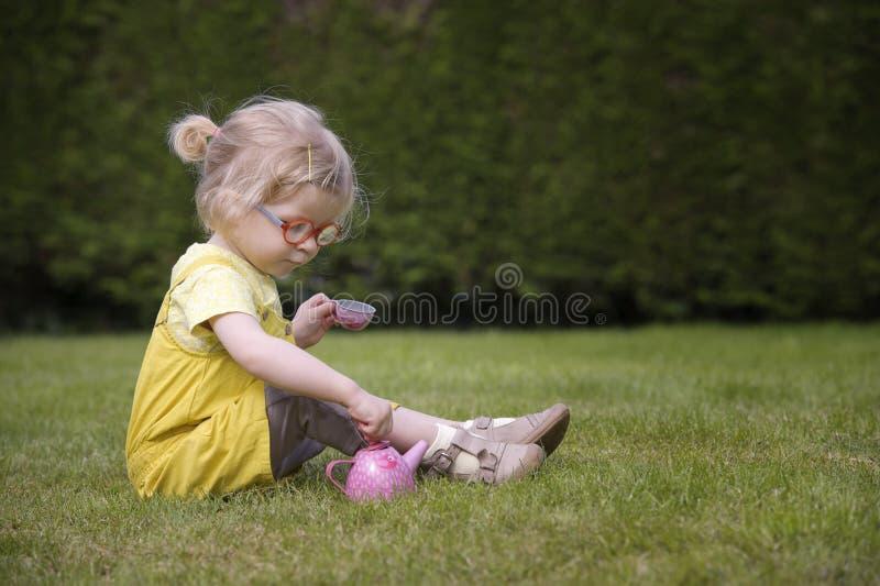 Маленький малыш играя время чая outdoors стоковые изображения rf