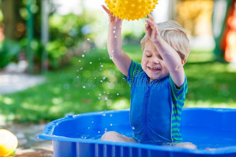 Download Маленький мальчик малыша имея потеху с брызгать воду в Gar лета Стоковое Фото - изображение насчитывающей детство, смешно: 37925422