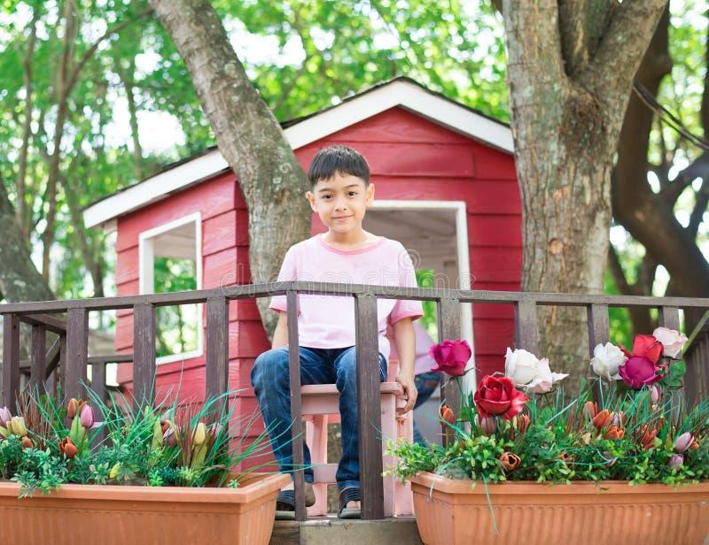 Маленький мальчик отпрыска сидя в доме на дереве есть мороженое стоковое фото