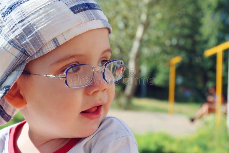 Маленький милый мальчик в стеклах и крышке смотрит отсутствующим и усмехается стоковая фотография