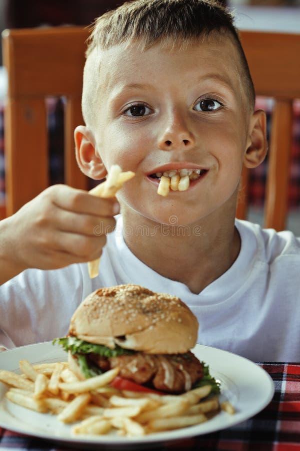 Маленький милый мальчик 6 лет с гамбургером и стоковое изображение
