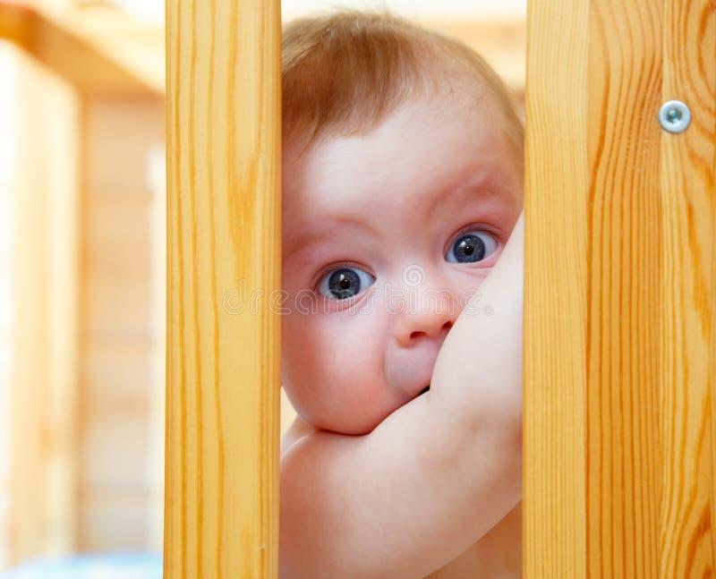 Маленький милый мальчик смотря через бортовую кроватку младенца стоковые изображения rf
