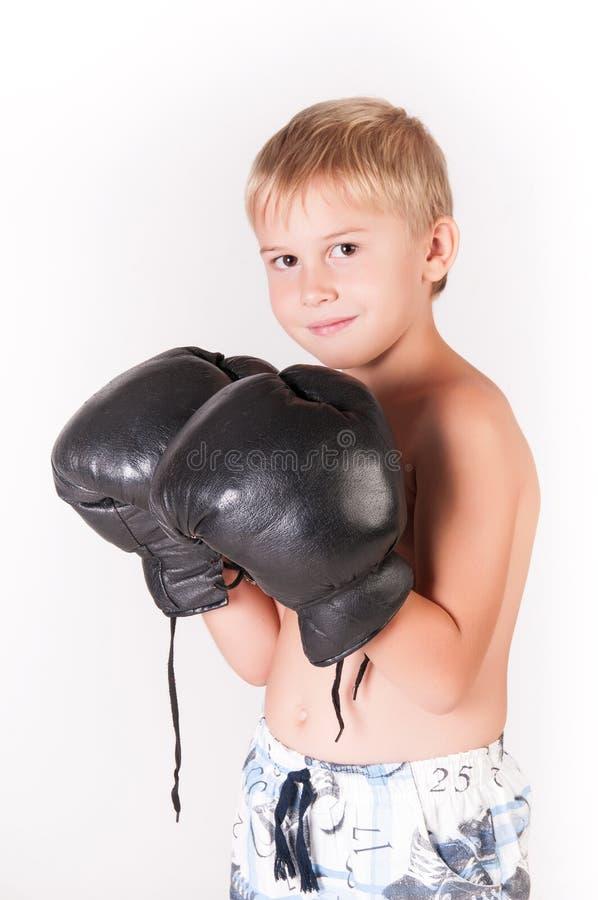 Маленький милый мальчик с перчатками бокса празднуя его победу на предпосылке пустой стены стоковые изображения rf