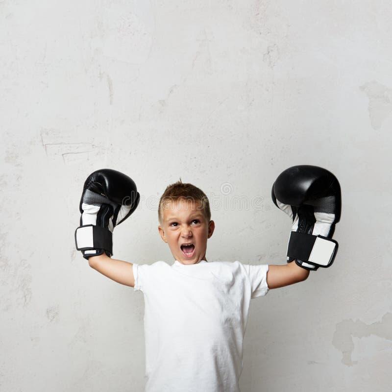 Маленький милый мальчик с перчатками бокса празднуя его стоковое фото