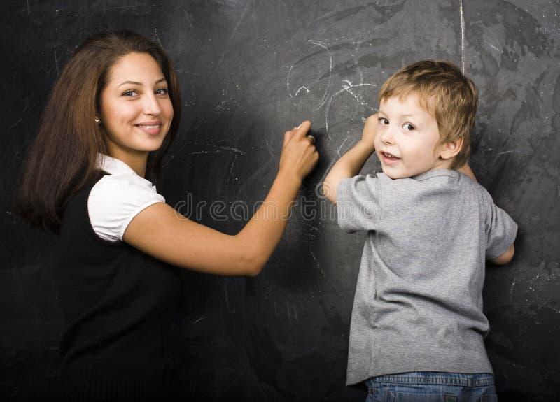 Маленький милый мальчик с учителем в классе стоковое изображение rf