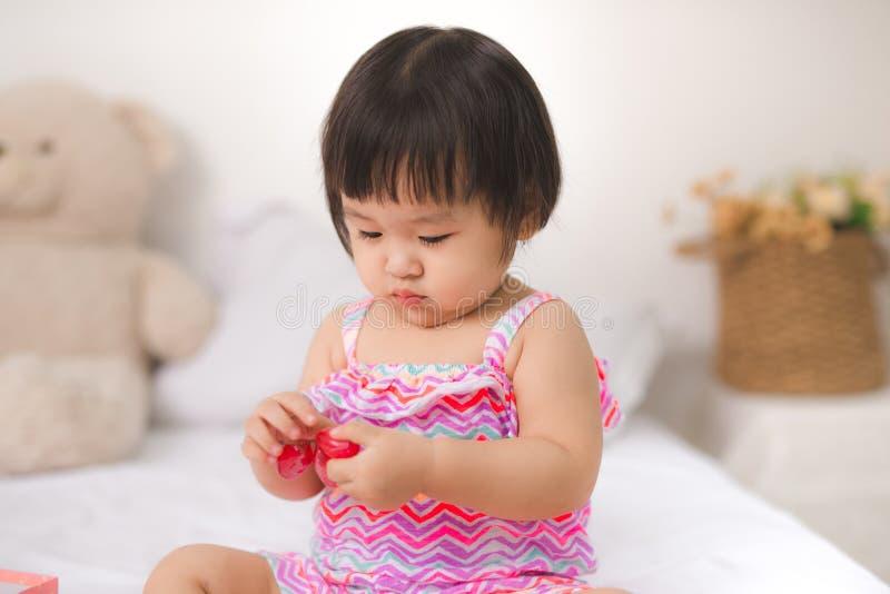 Маленький милый ребёнок сидя на кровати с виноградинами стоковая фотография