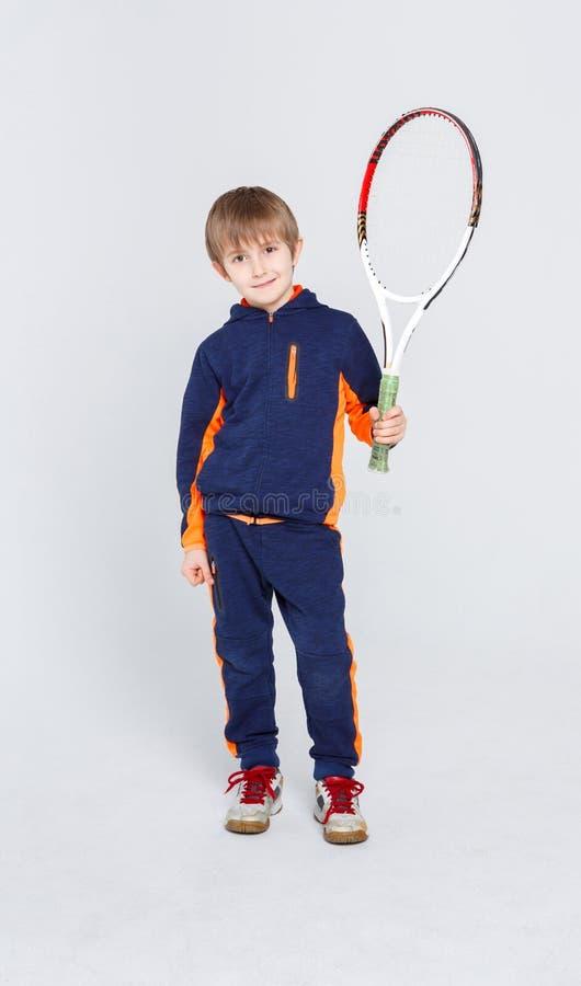 Маленький милый теннисист в sportswear с ракеткой на предпосылке студии стоковое фото