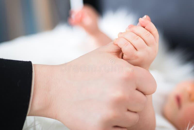 Маленький младенец держа руку матерей стоковое изображение