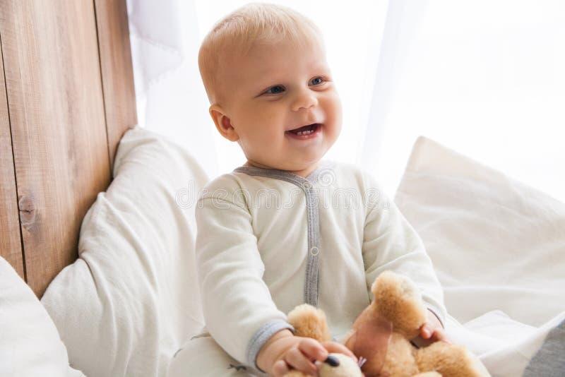 Маленький младенец усмехаясь и смотря прочь стоковое изображение