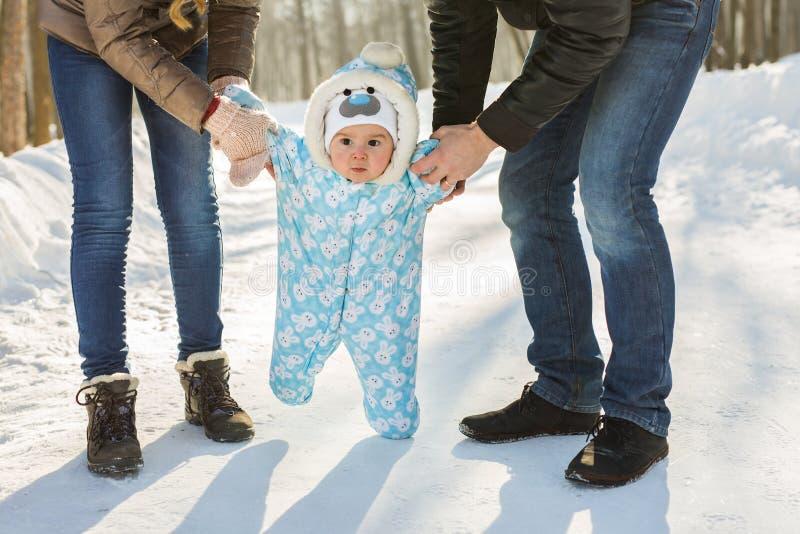 Маленький младенец уча идти Мать и отец с мальчиком малыша на зиме паркуют стоковое изображение rf