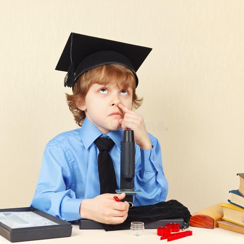 Маленький профессор в мысли академичной шляпы смешной, видя что-то в микроскопе стоковое фото