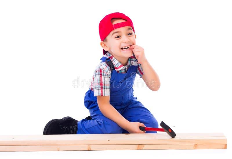 Маленький плотник ударил его палец пока пригвождающ стоковая фотография rf