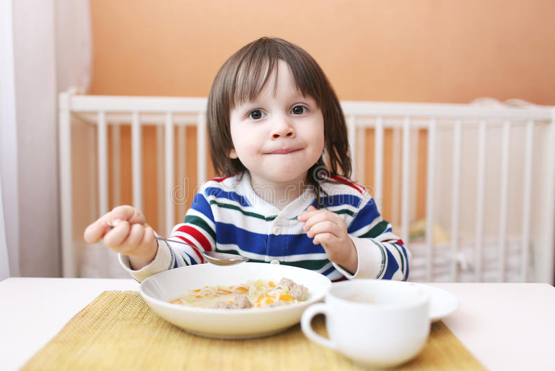 Маленький ребенок ест суп стоковое фото rf