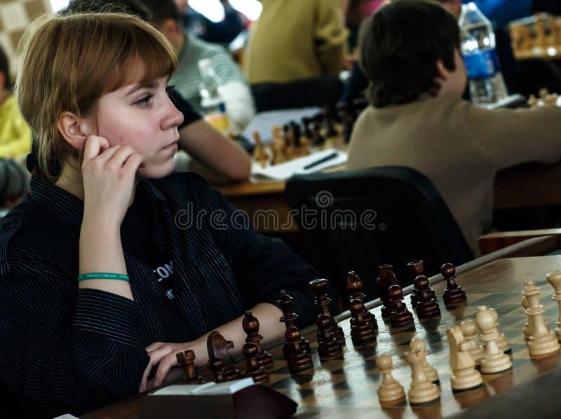 Маленький ребенок делая движение с лошадью во время турнира шахмат на школе, с несколькими других конкурентов на заднем плане стоковое фото