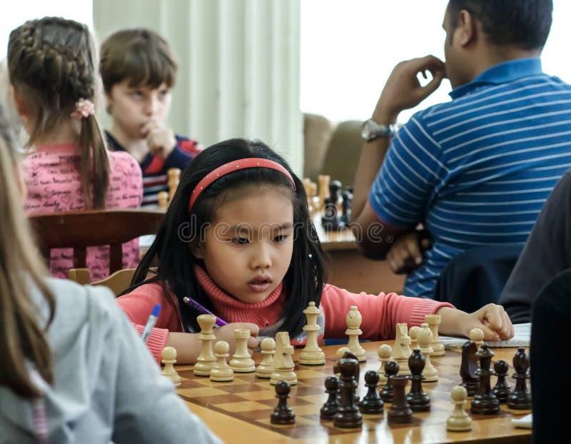 Маленький ребенок делая движение с лошадью во время турнира шахмат на школе, с несколькими других конкурентов на заднем плане стоковое изображение rf