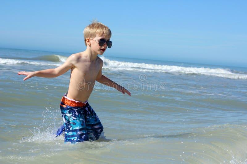 Маленький ребенок идя в воду океана стоковая фотография rf