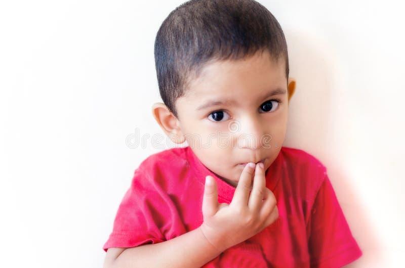 маленький ребенок кладя палец на рот с малыми волосами стоковое изображение rf