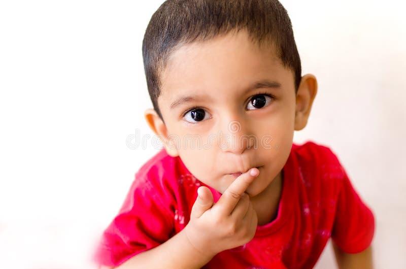 маленький ребенок кладя палец на рот с малыми волосами стоковые изображения rf