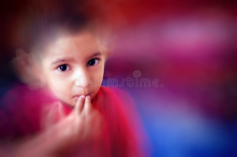 маленький ребенок кладя палец на рот с малыми волосами стоковая фотография