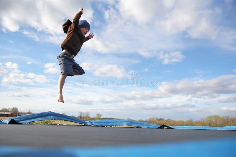 Маленький ребенок скача на внешний батут семьи стоковые фотографии rf