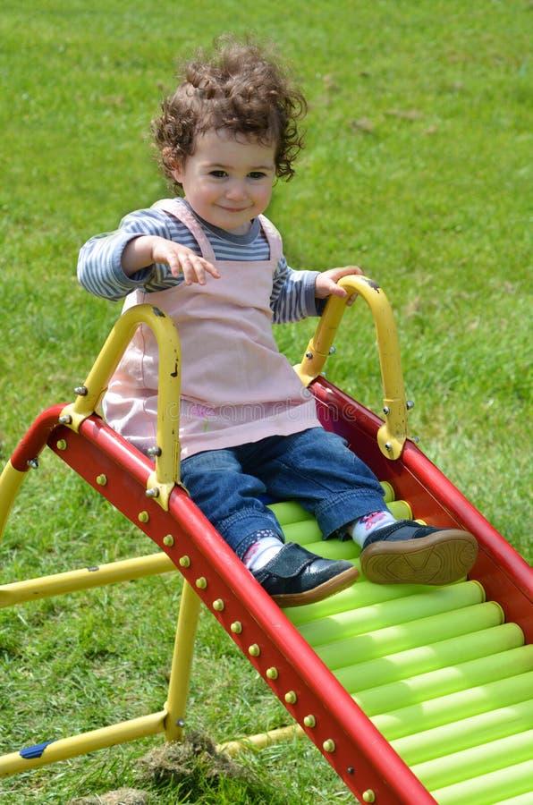 Маленький ребенок сползая на скольжение стоковые фотографии rf