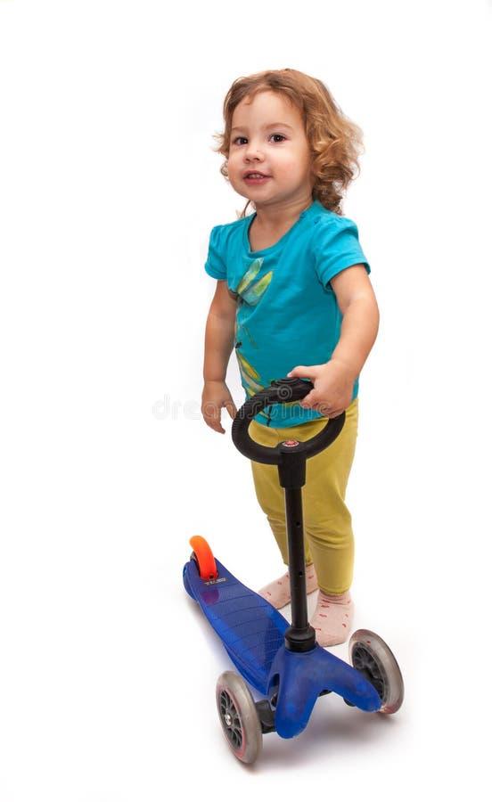 Маленький ребенок стоя близко самокат стоковое изображение
