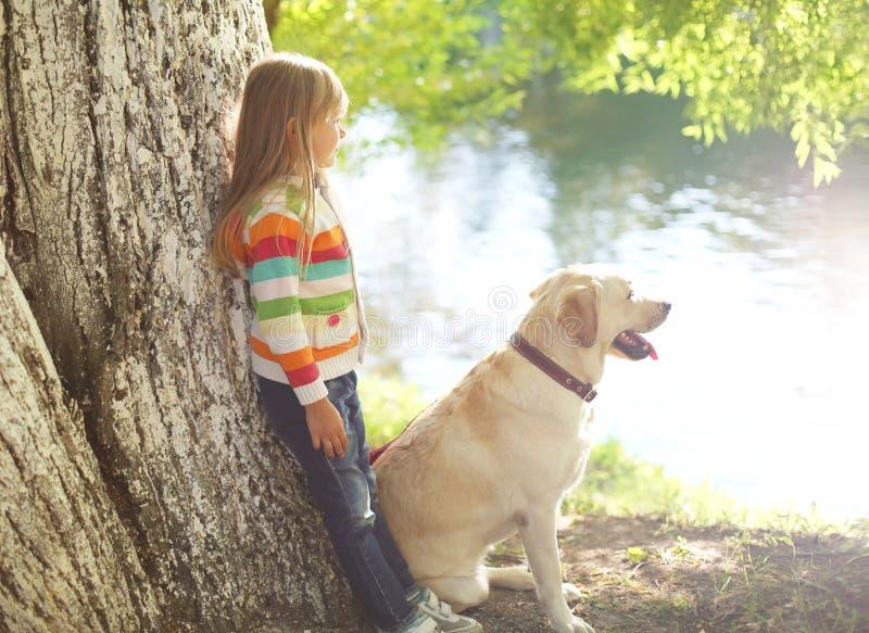 Маленький ребенок с собакой retriever Лабрадора в парке лета стоковое изображение