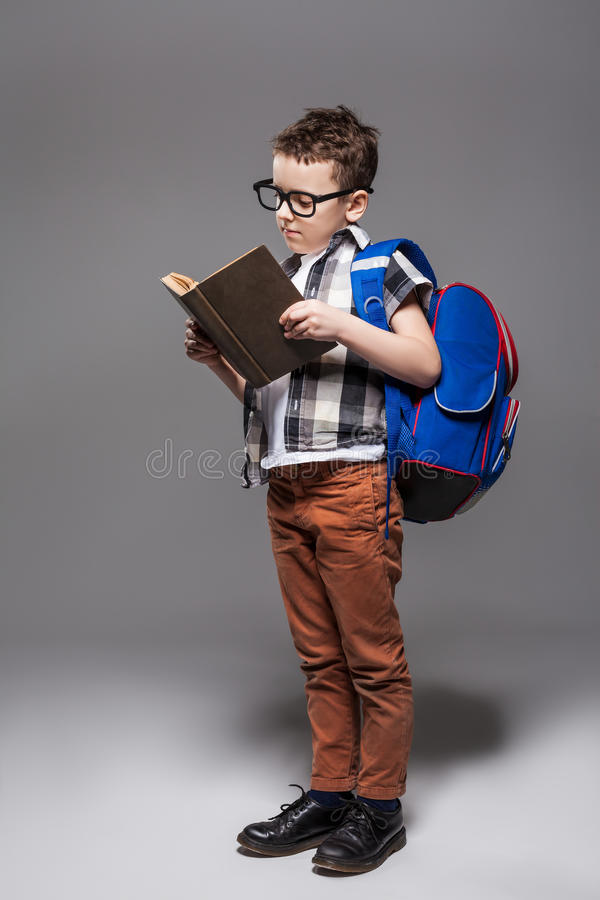 Маленький ребенок с сумкой школы и книга в студии стоковая фотография
