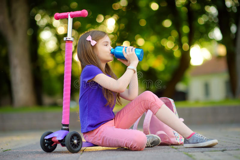 Маленький ребенок уча ехать самокат в парке города на солнечный летний день Милая девушка preschooler в шлеме безопасности ехать  стоковые изображения rf