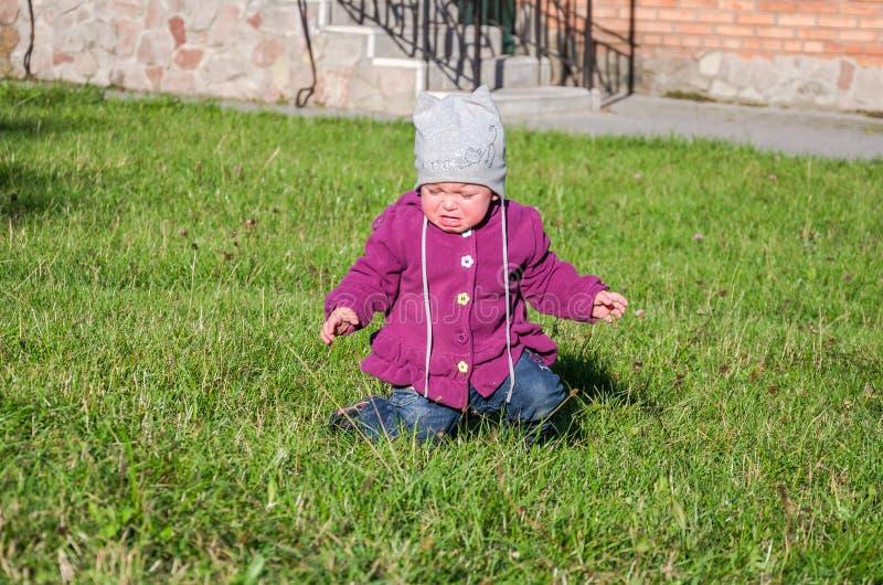Маленький ребёнок в джинсах куртке и шляпе делая учить идти его первые шаги на лужайке в зеленой траве она имеет очень не пойти стоковые изображения