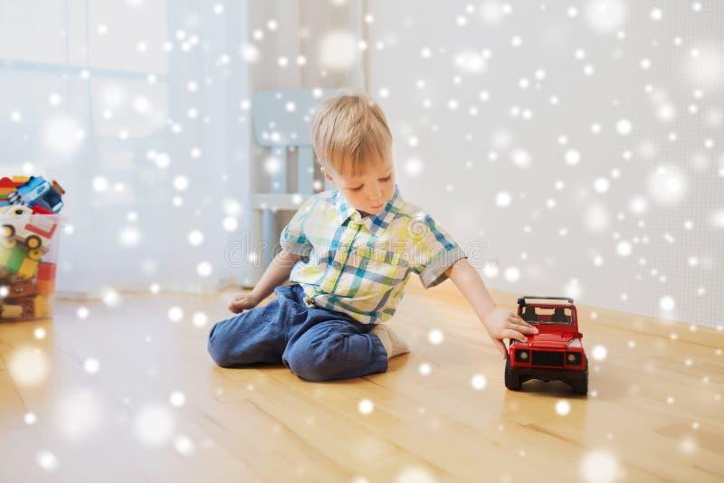 Маленький ребёнок играя с автомобилем игрушки дома стоковое изображение rf