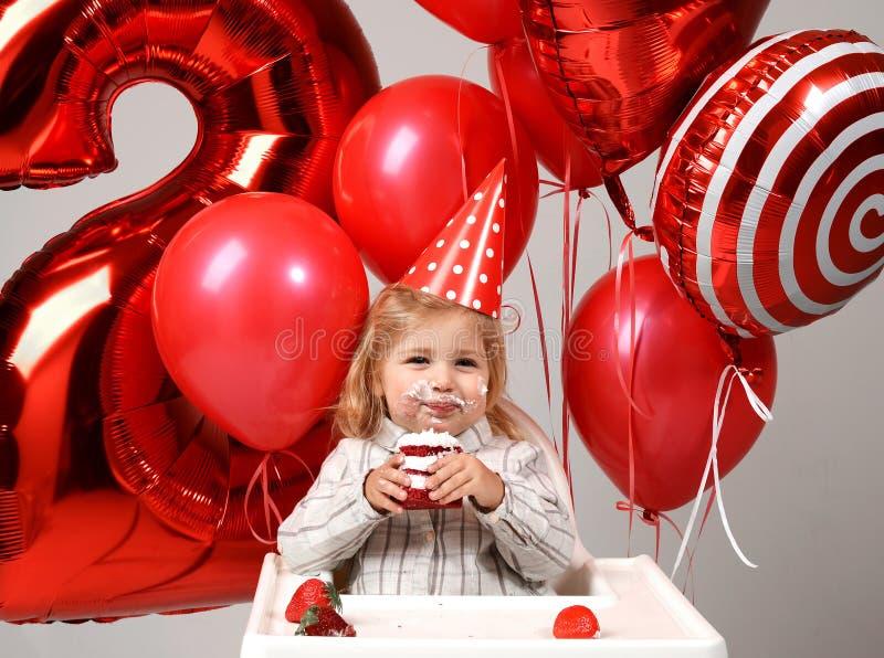 Маленький ребёнок празднует ее второй день рождения с сладостным тортом o стоковая фотография rf