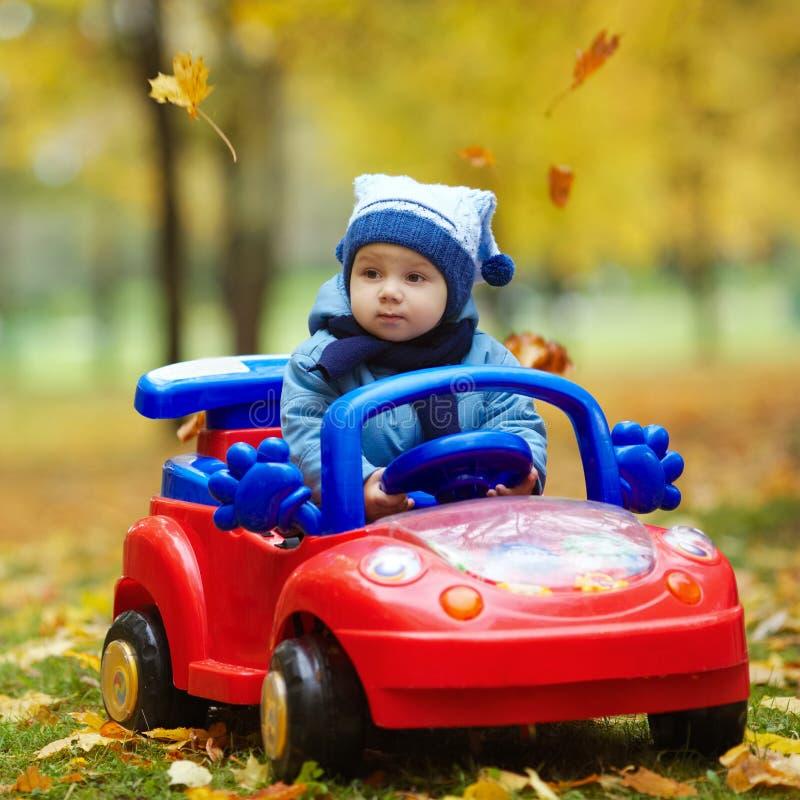 Маленький смешной мальчик управляя автомобилем игрушки стоковые изображения