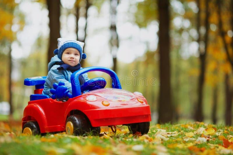 Маленький смешной мальчик управляя автомобилем игрушки стоковые изображения rf