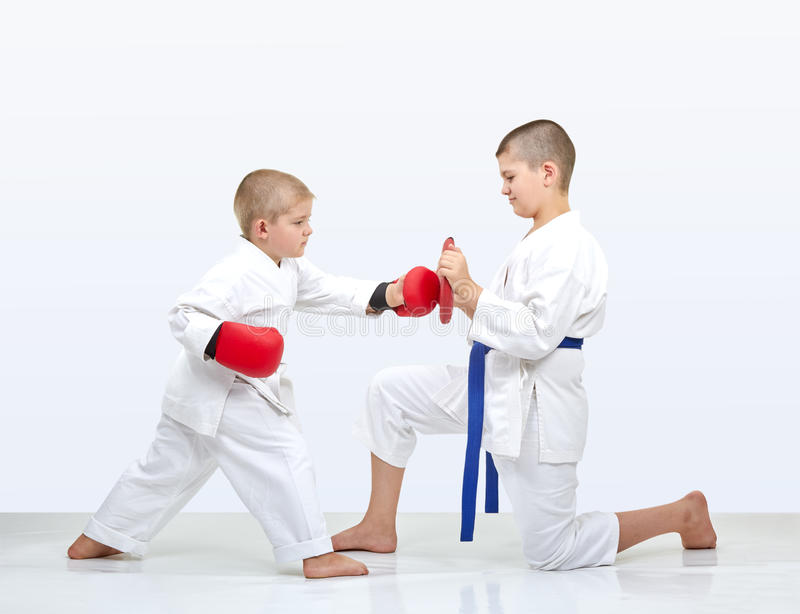 Маленький спортсмен бьет пунш makiwara которое держит брата стоковое изображение rf