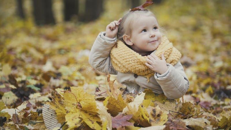 Маленький счастливый ребёнок играет в парке осени среди желтых листьев стоковое фото rf