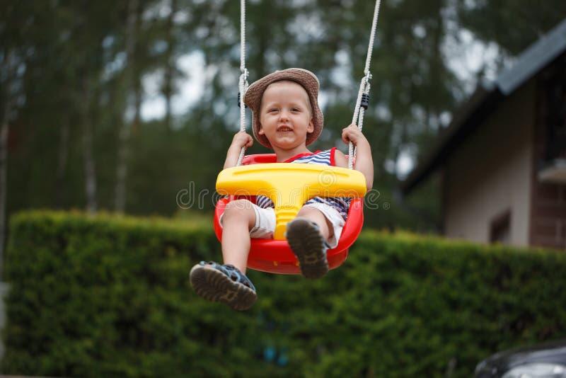Маленький усмехаясь мальчик имея потеху и отбрасывая на внешнем playgroun стоковое изображение