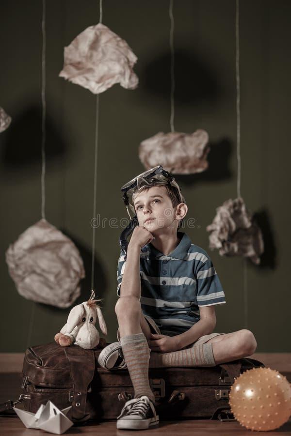 Маленький фантазер сидя на чемодане стоковые фотографии rf