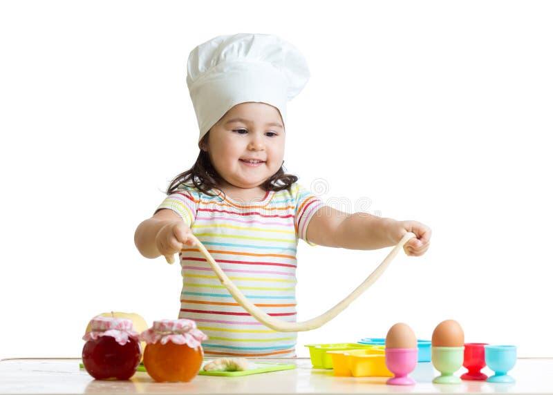 Маленький шеф-повар играя с тестом стоковое изображение