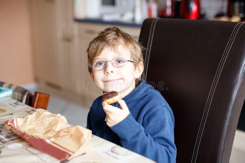 Маленький школьник есть донут крытый в буфете стоковые фотографии rf
