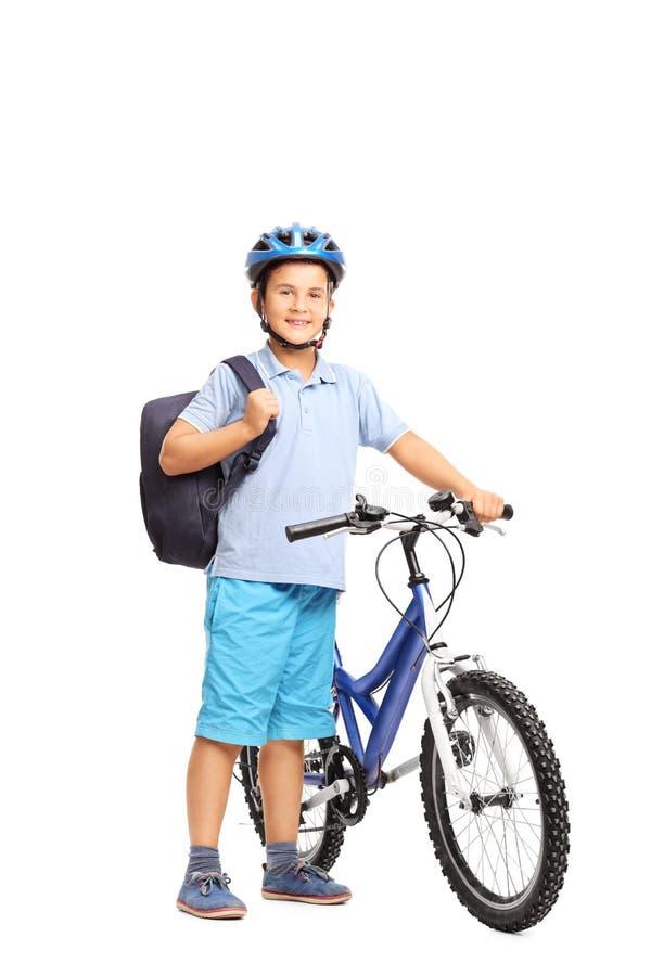 Маленький школьник представляя рядом с его велосипедом стоковые фотографии rf