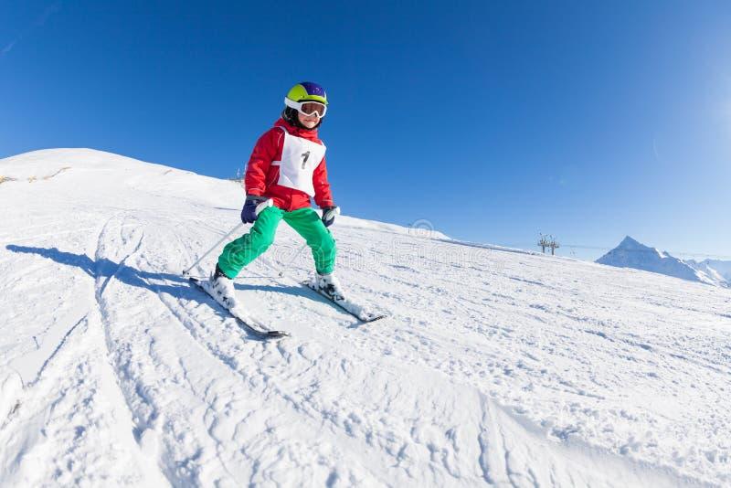 Маленький лыжник ударяя наклон в высокогорный курорт стоковые изображения rf