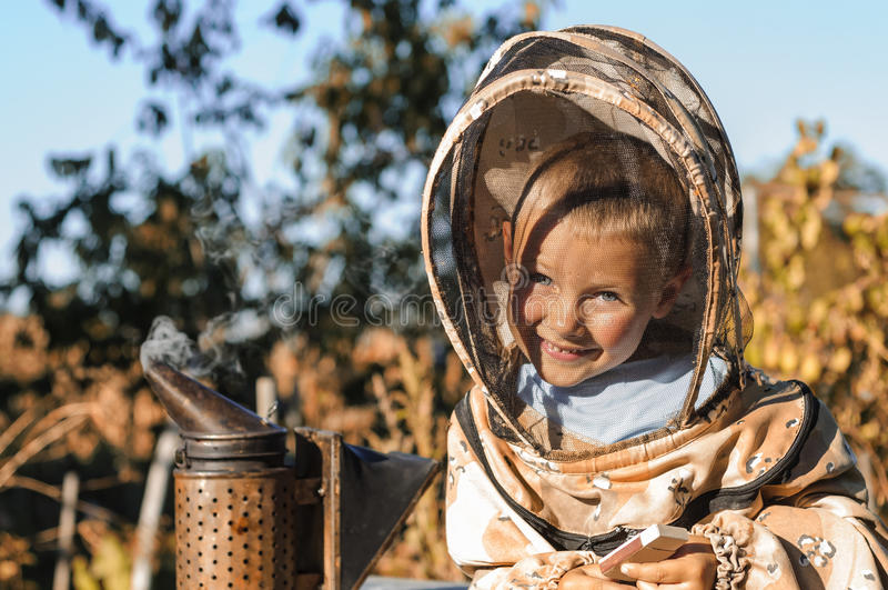 Маленький beekeeper дует курильщик для пчел стоковая фотография