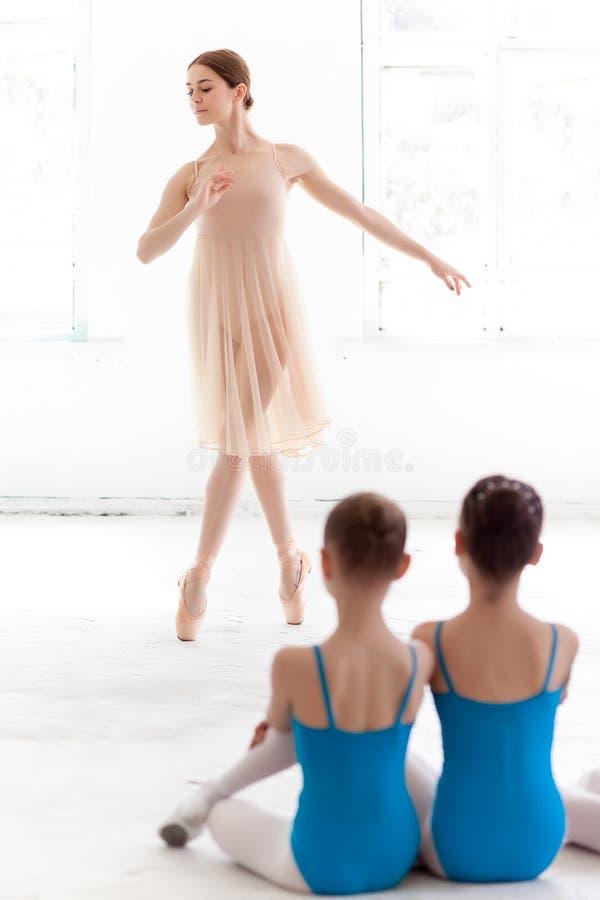 2 маленьких балерины танцуя с личным учителем балета в студии танца стоковые фото
