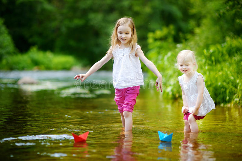 Download 2 маленьких сестры играя с бумажными шлюпками Стоковое Изображение - изображение насчитывающей потеха, семья: 41660495