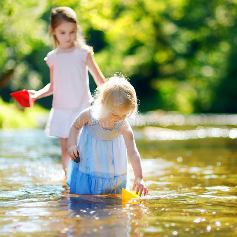 2 маленьких сестры играя с бумажными шлюпками стоковые фотографии rf